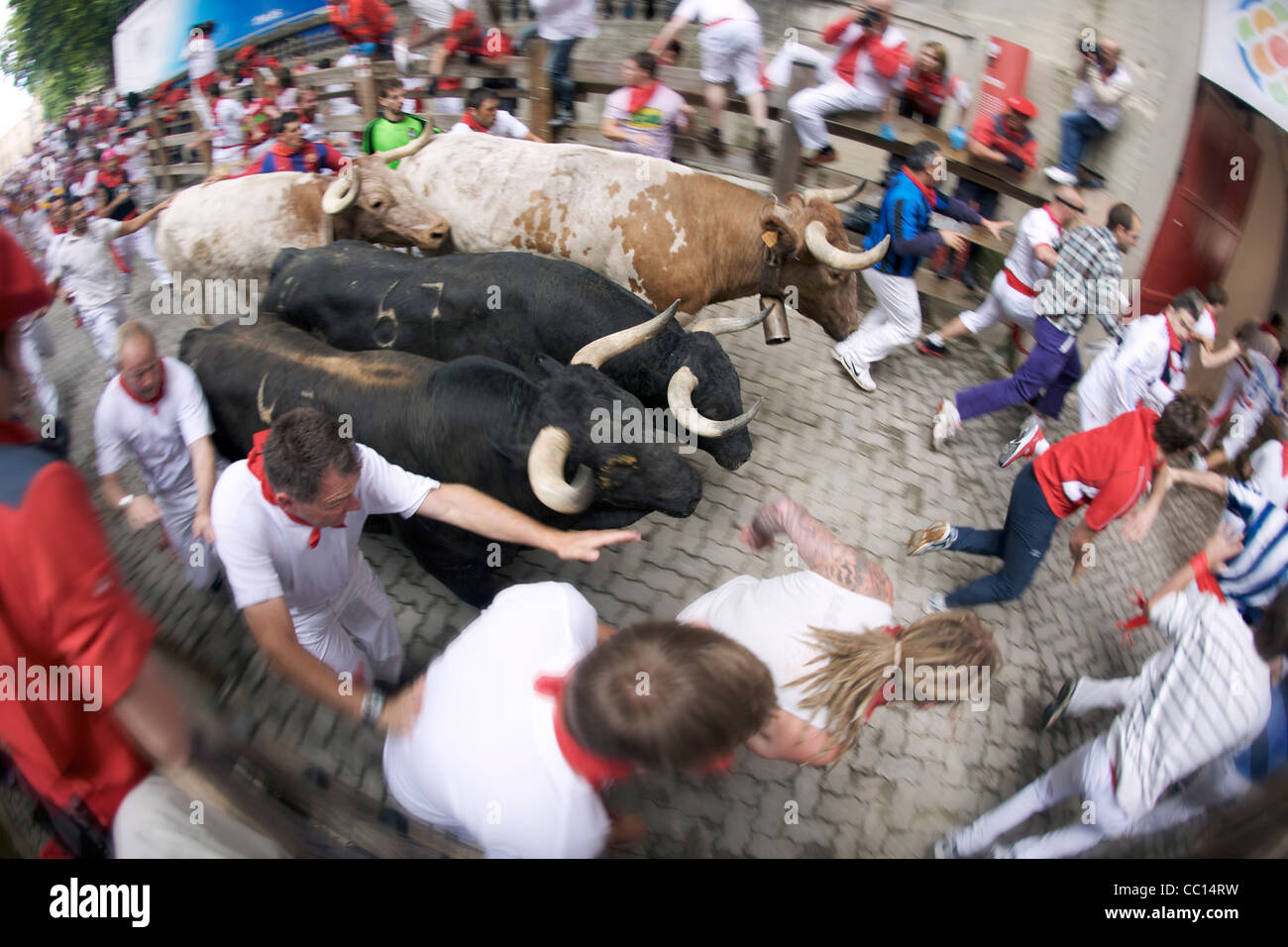 Crowds running with bulls during the annual festival of San Fermin (aka the running of the bulls) in Pamplona, Spain. Stock Photo