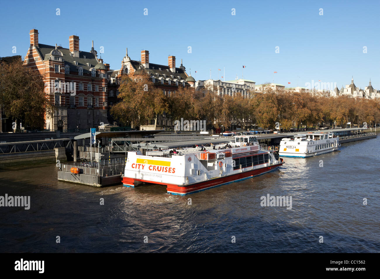London river cruise boats at the westminster millennium pier on the river thames England UK United kingdom Stock Photo