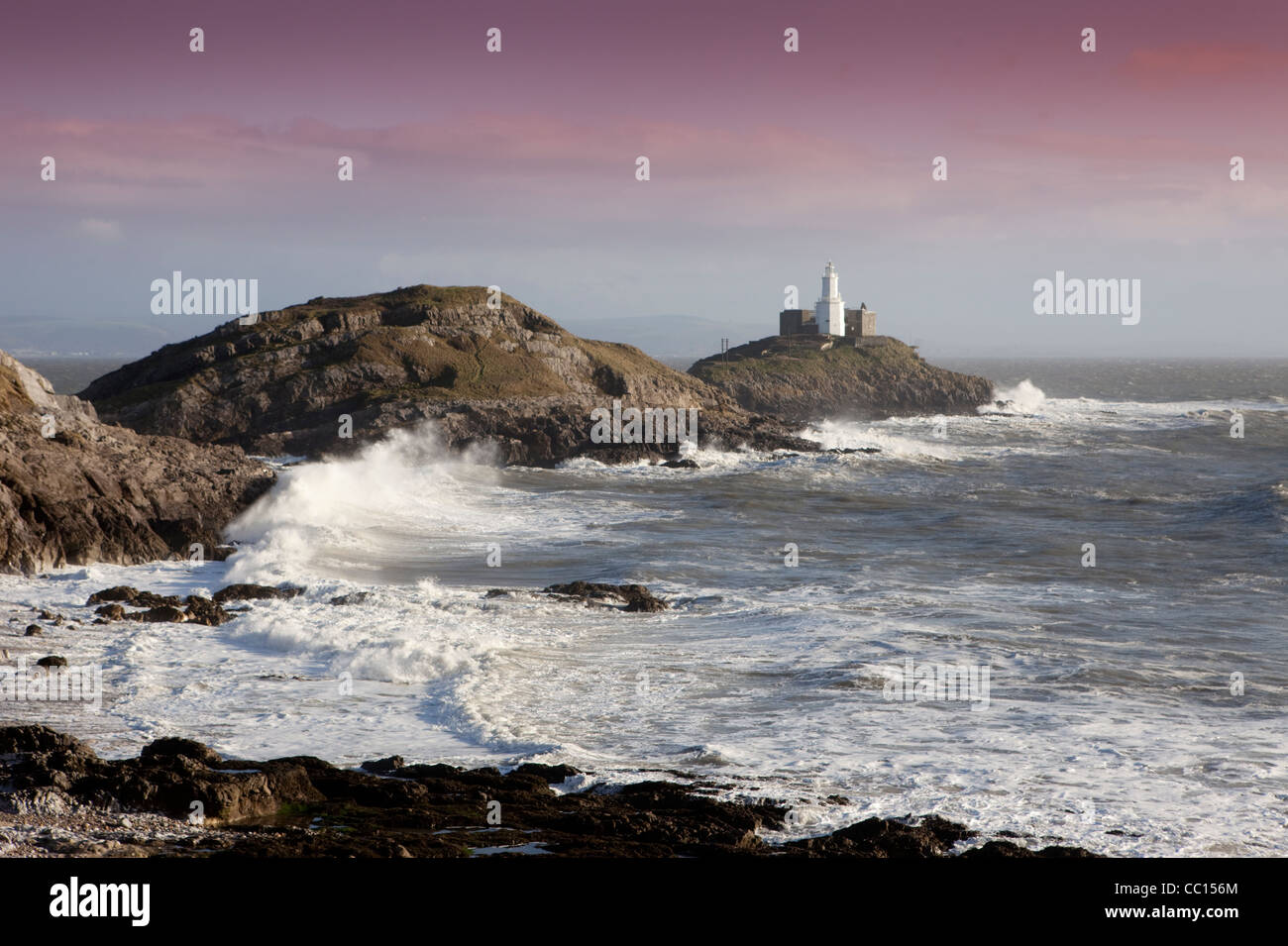 Waves crash against Mumbles headland and the lighthouse as gales sweep across the United Kingdom. - Stock Image