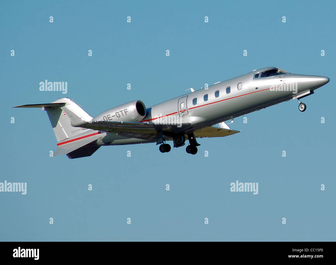 Bombardier Learjet 60 business jet (with Austrian registration OE-GTF) climbs away from London Luton Airport, England. - Stock Image