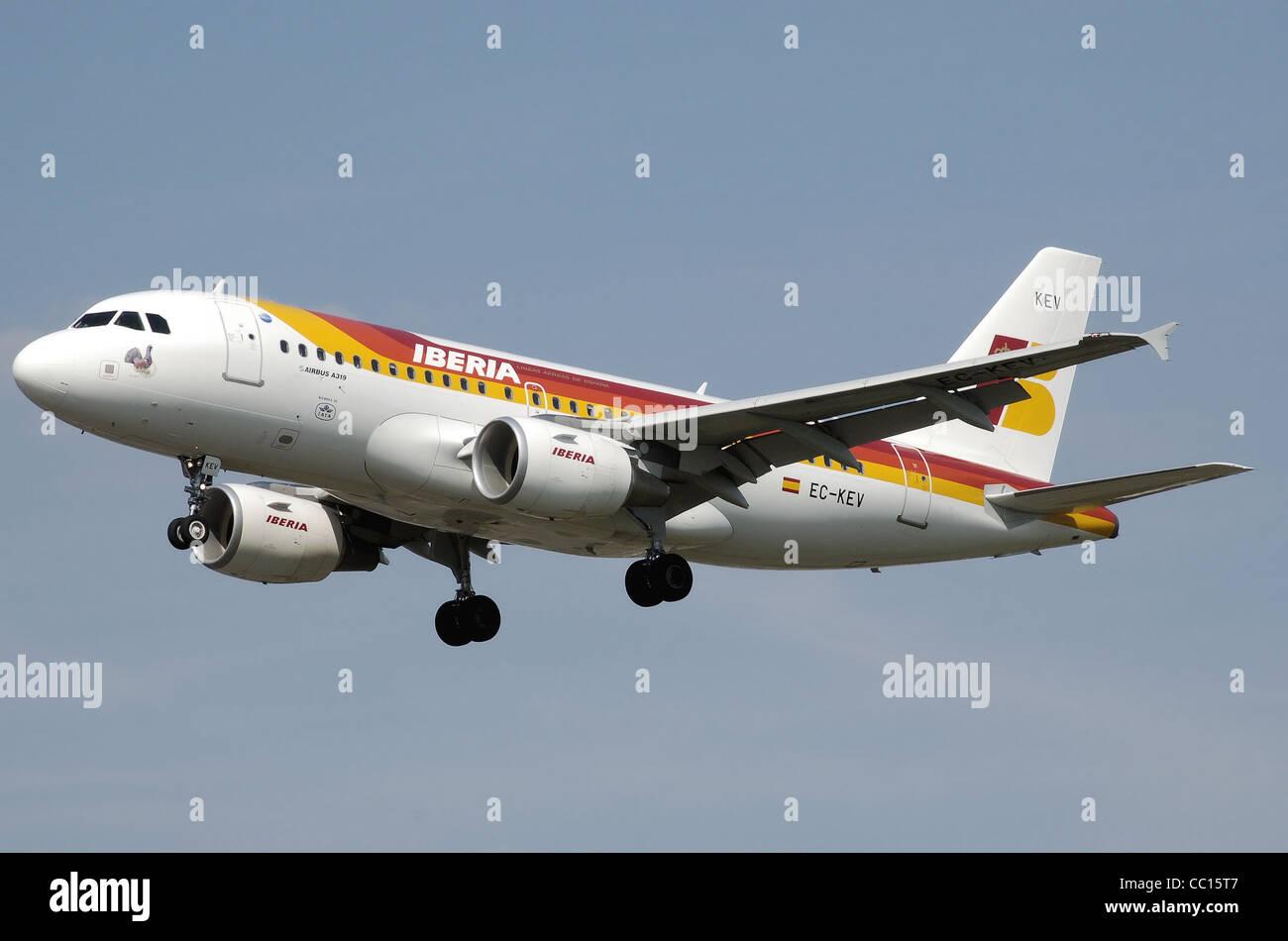Iberia Airbus A319-100 (EC-KEV) landing at London Heathrow Airport. - Stock Image