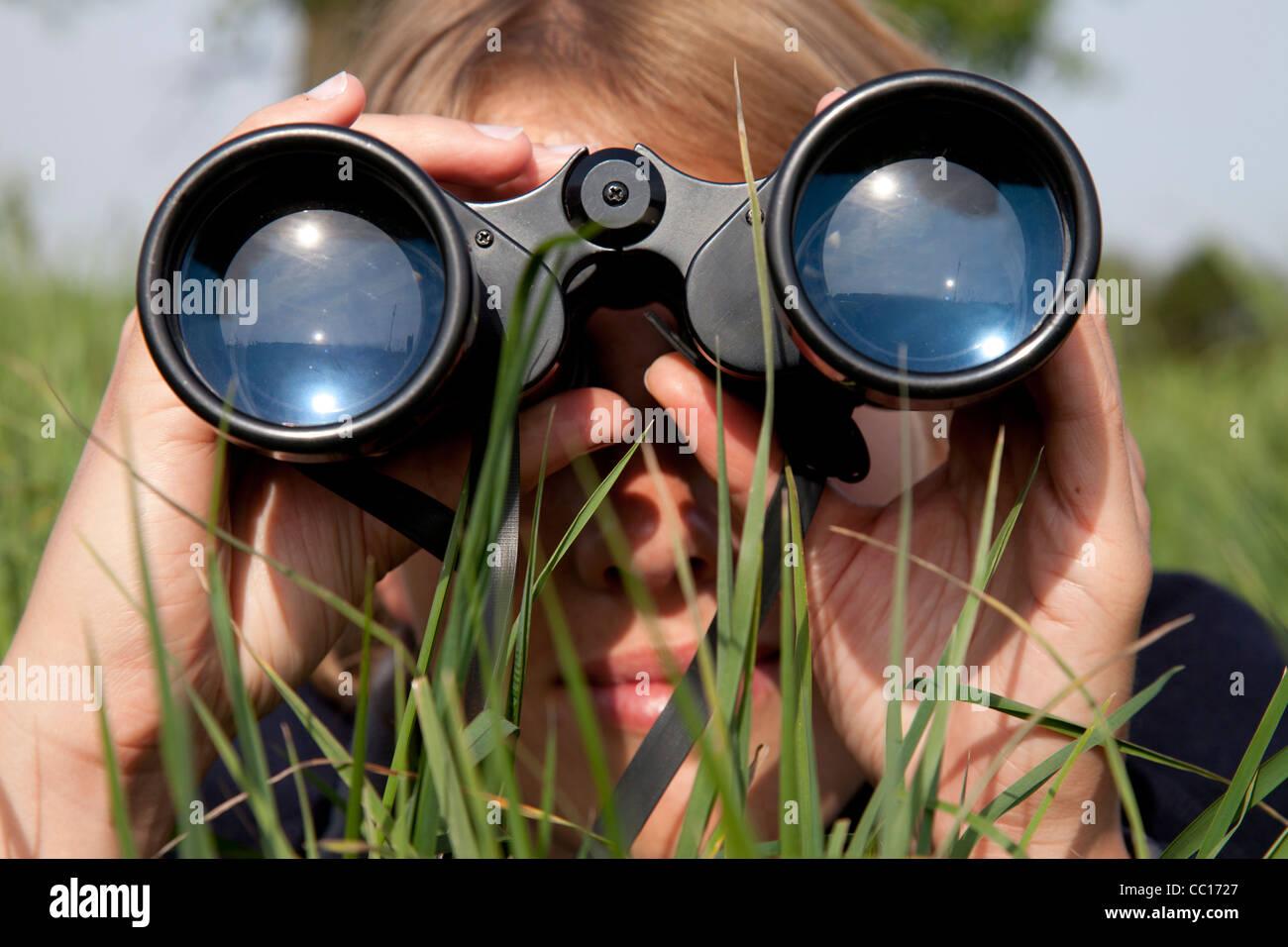 Looking through binoculars - Stock Image