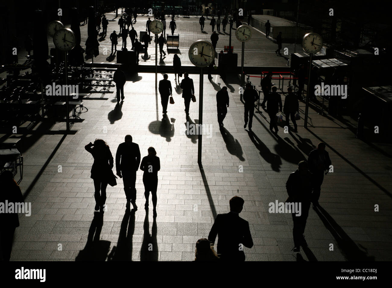 Shadows and silhouettes of pedestrians walking through Reuters Plaza, Canary Wharf, London, UK Stock Photo