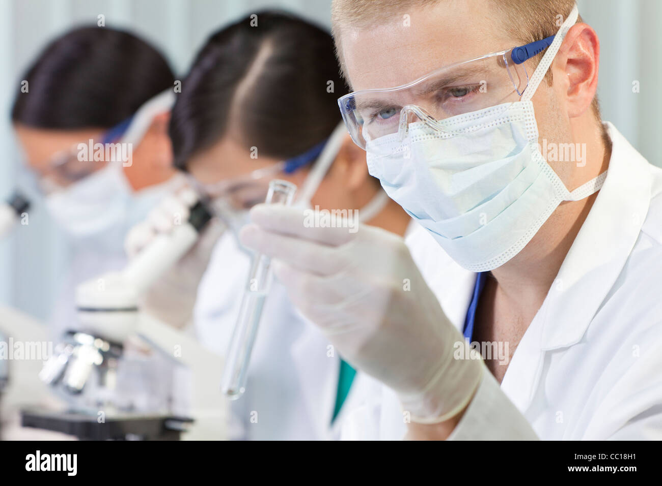 A male medical or scientific researcher or doctor looking at a test tube of clear liquid in a laboratory with microscopes - Stock Image