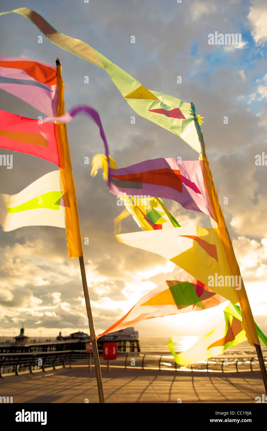 Colourful flags fluttering in the wind on Blackpool Promenade at sunset - Stock Image