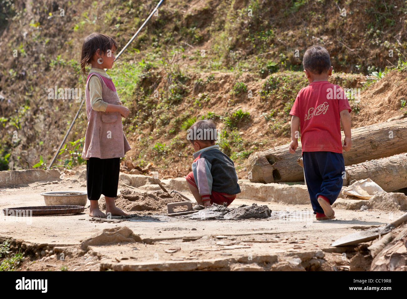 Three children in a Vietnamese village near Sapa who appear to be mixing cement - Stock Image