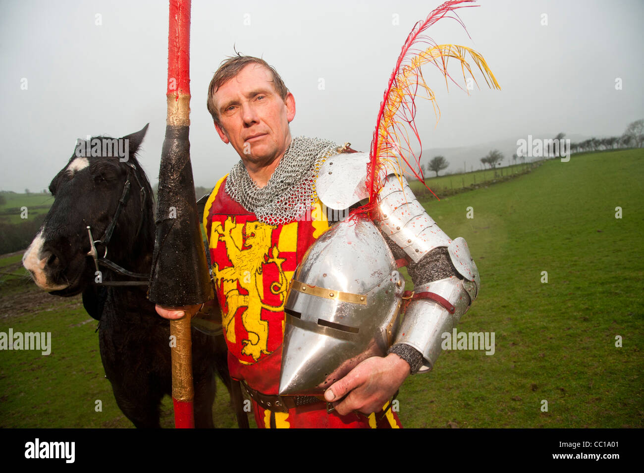 Sheep farmer and champion medieval jouster Philip Hughes - Sir Philip of Argoed - with his horse on his farm in - Stock Image