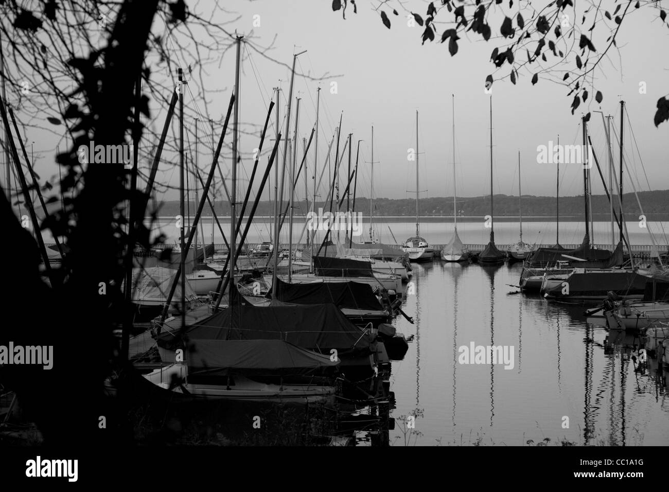 Black and white silhouette photo of a small harbour in the evening on the Starnberger Lake in Bavaria, Germnay. - Stock Image