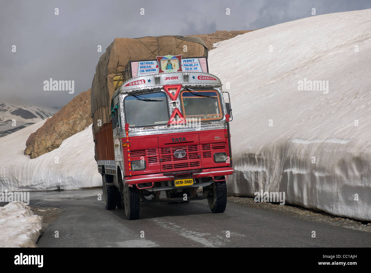Tata truck driving past snow drifts by the side of the road, Baralach La pass, Leh-Manali Highway, Himachal Pradesh, - Stock Image