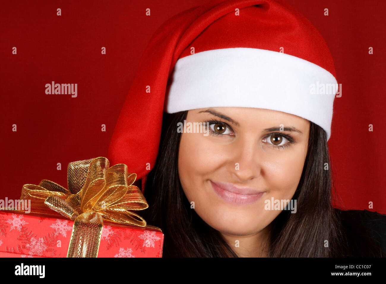 Beautiful 18 years old Santa Claus girl offering a Christmas present ...