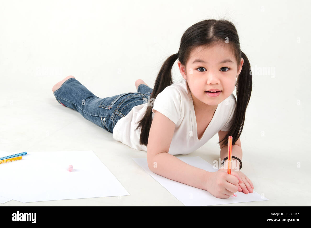 Little Asian Girl Drawing Lying On Floo