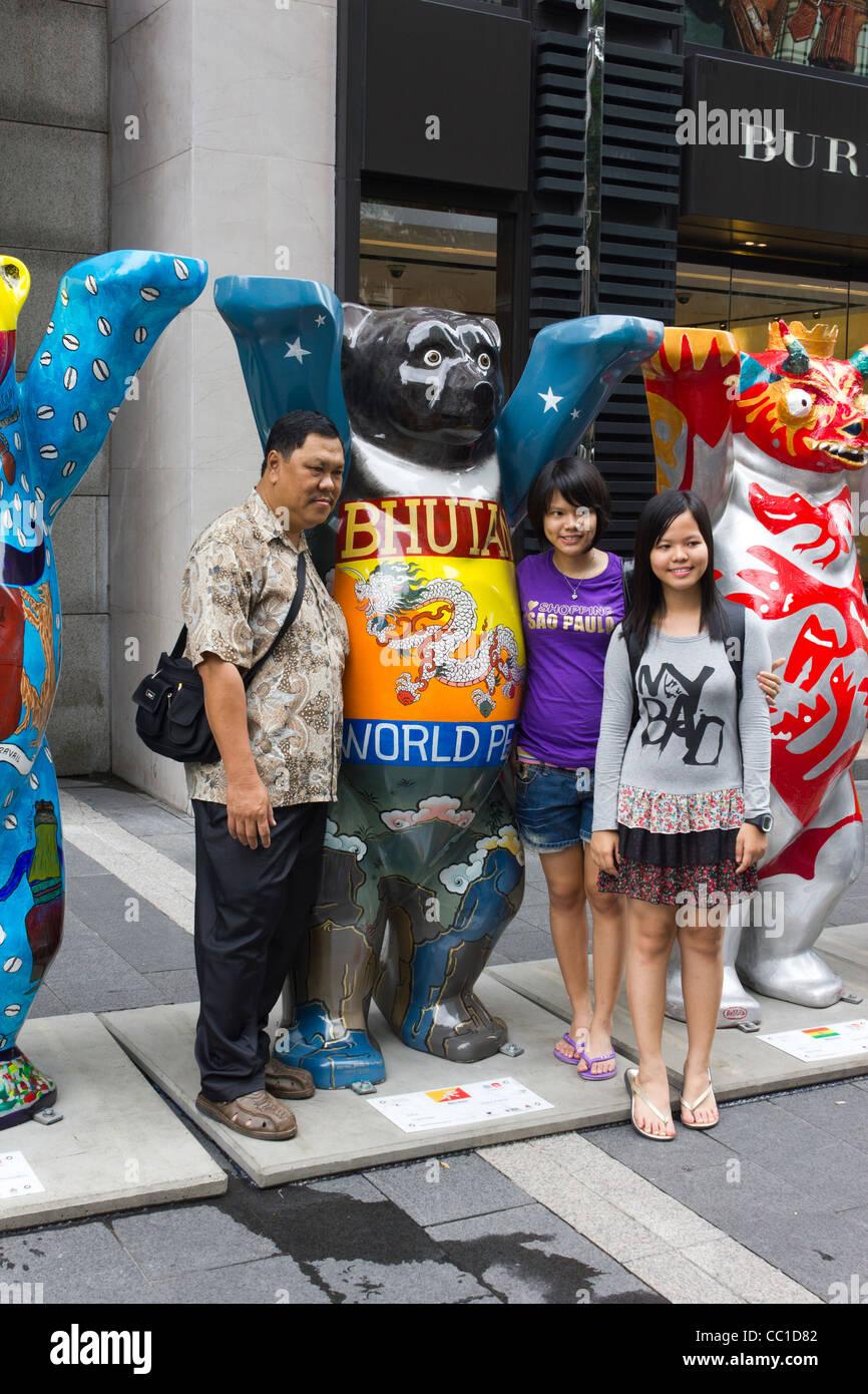 family  posing for photograph, United Buddy Bears exhibition, Pavilion Mall, Kuala Lumpur, Malaysia - Stock Image