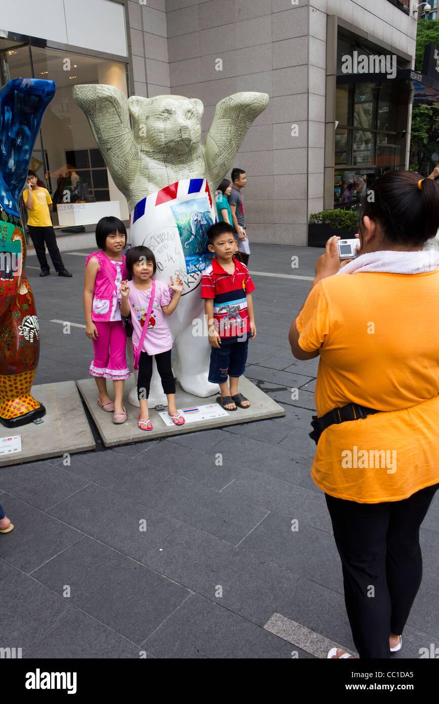 children posing for photograph, United Buddy Bears exhibition, Pavilion Mall, Kuala Lumpur, Malaysia - Stock Image