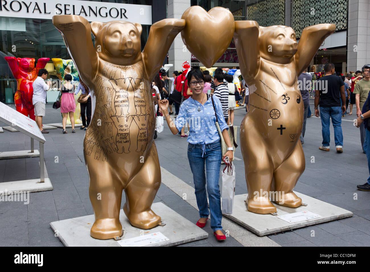 girl posing for photograph, United Buddy Bears exhibition, Pavilion Mall, Kuala Lumpur, Malaysia - Stock Image