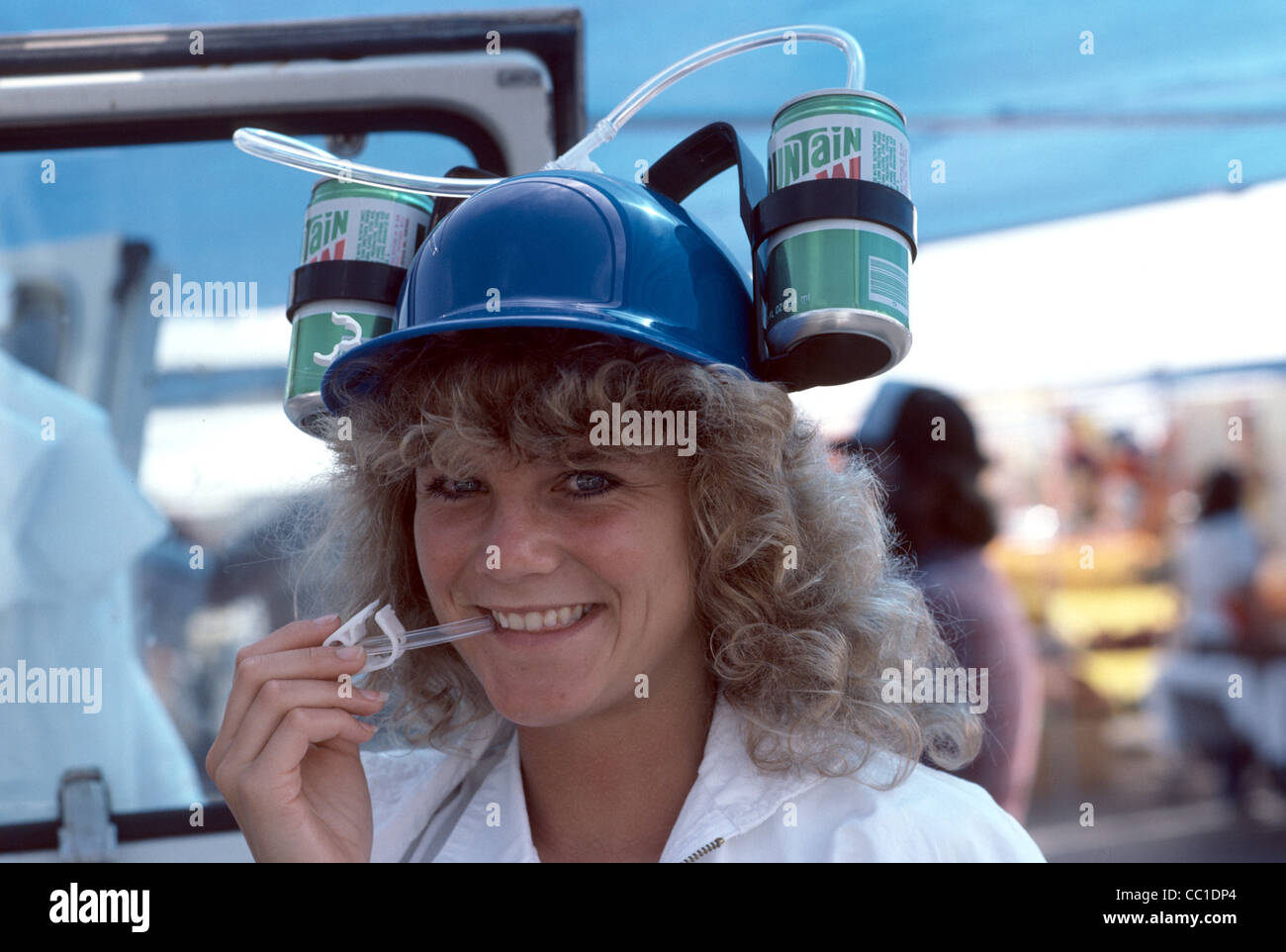 1970's image of silly hat with soda pop connected to brim and straw reaching the mouth - Stock Image