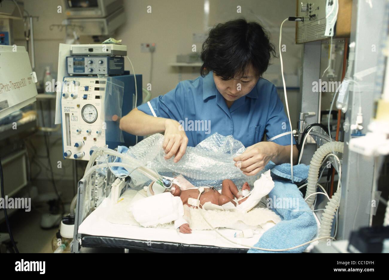 Nurse Tending Baby In Neonatal Intensive Care Unit Stock Photo