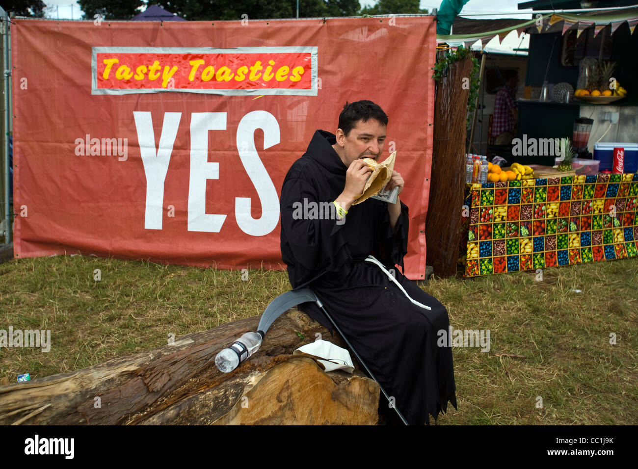 A man dressed as the Grim Reaper eats a sandwich on a log at the Standon Calling Festival in Hertfordshire, UK. - Stock Image