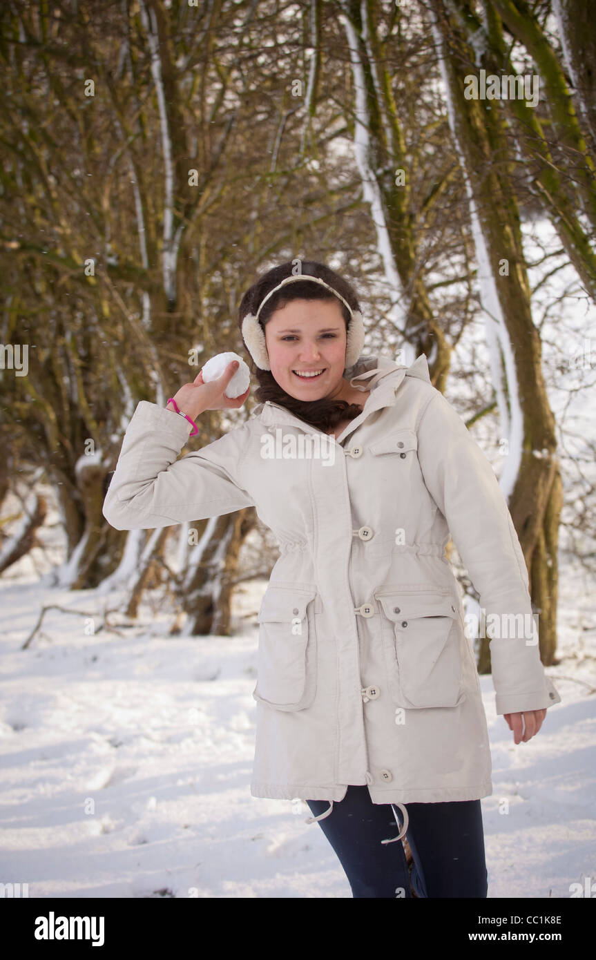 Young girl outdoors in snow throwing snowball - Stock Image