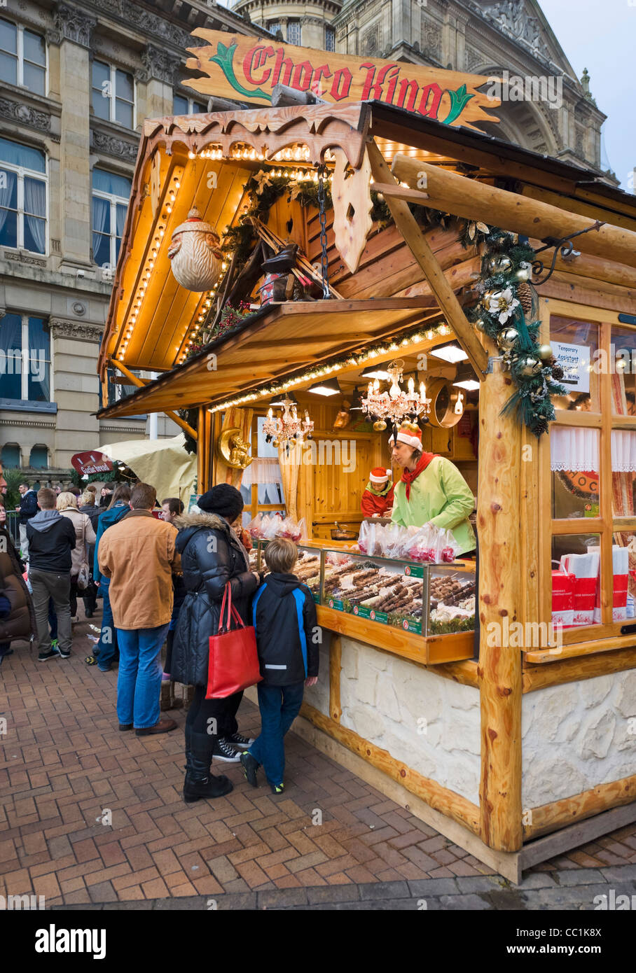 Family in front of a stall selling chocolate at the Frankfurt German Christmas Market, Victoria Square, Birmingham, - Stock Image