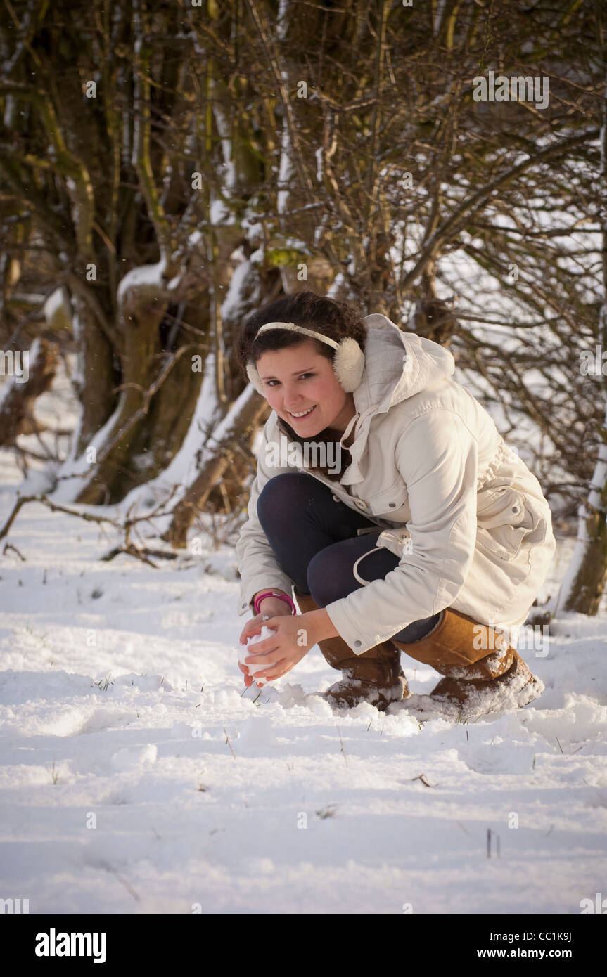 Young woman outdoors making snowball - Stock Image