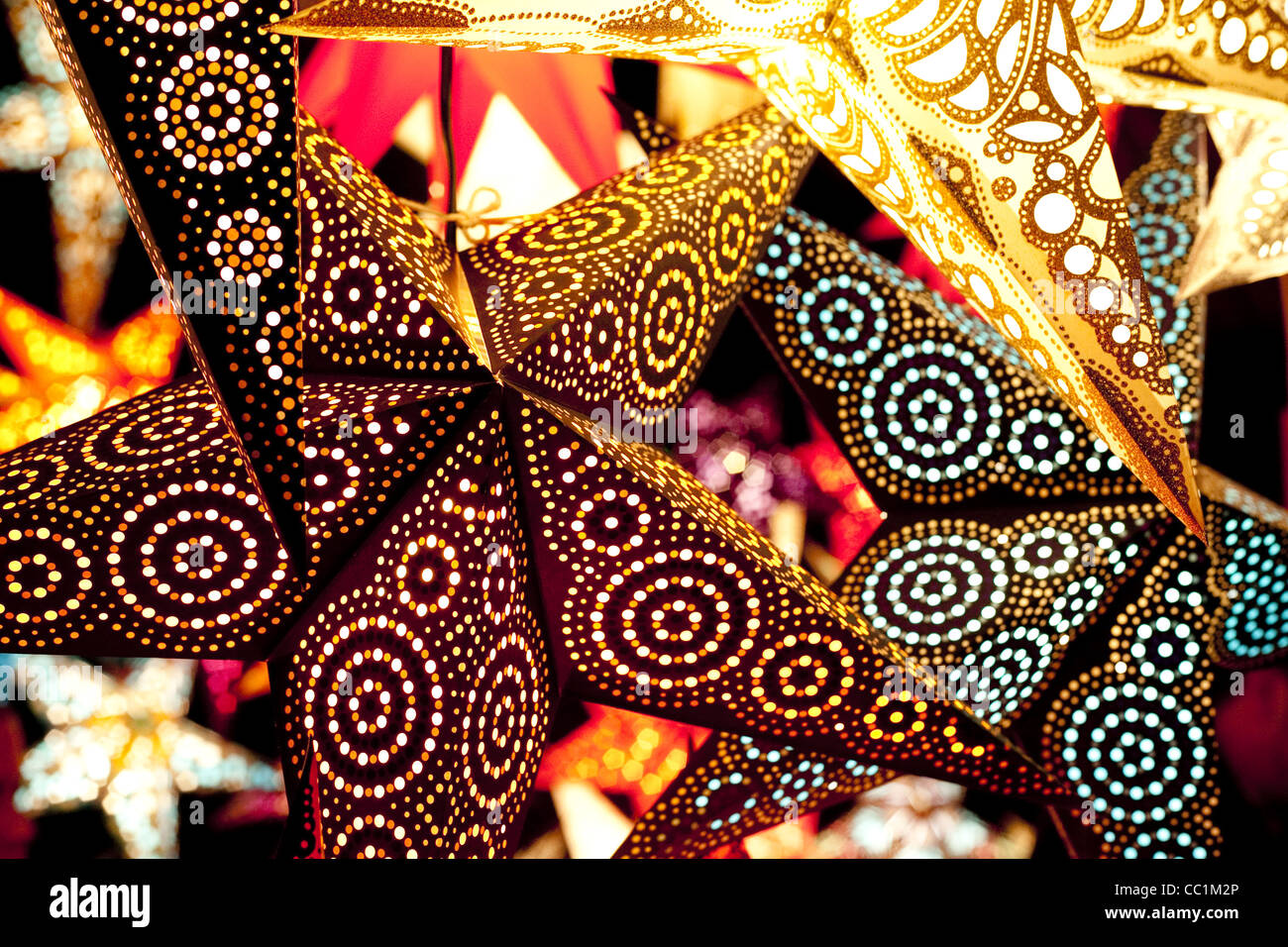 Bright colourful and dynamic lit up paper stars hang in a Christmas market in Munich, Germany. - Stock Image