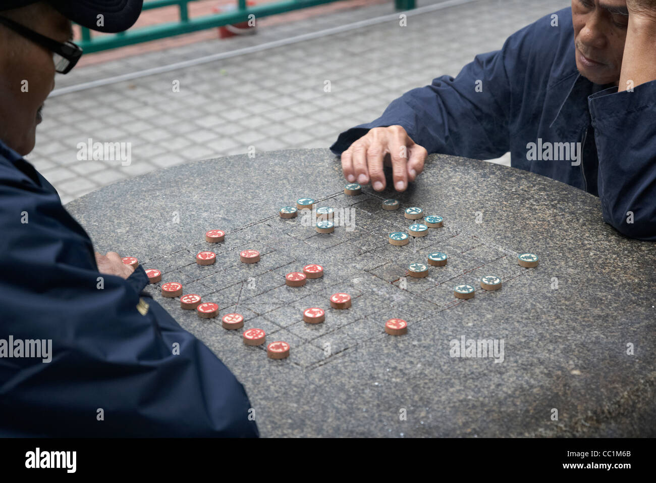 chinese men playing chinese chess at an outdoor municipal park table in hong kong hksar china asia - Stock Image