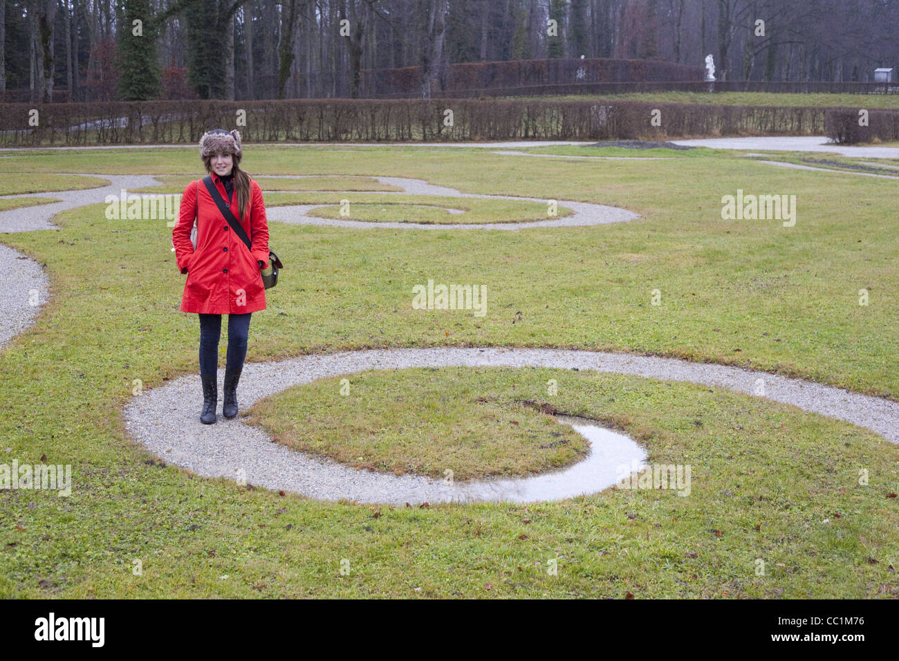 A girl with a red jacket walks a spiral path in a green garden at the Herreninsel Palace built by King Ludwig II. - Stock Image