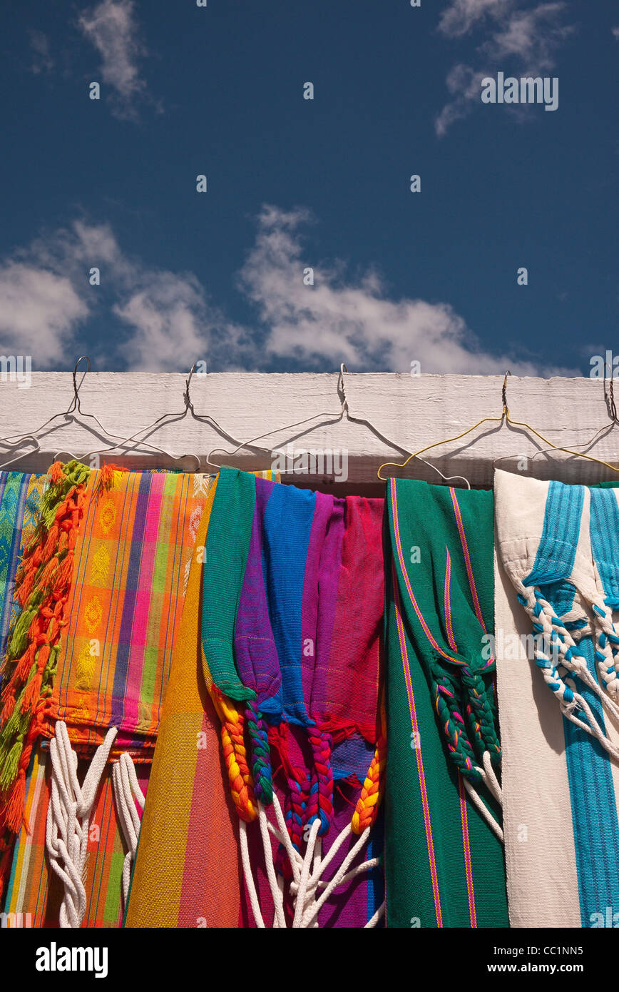 A variety of very colorful cloth weavings hang in a display at the market in Otavalo, Ecuador. - Stock Image