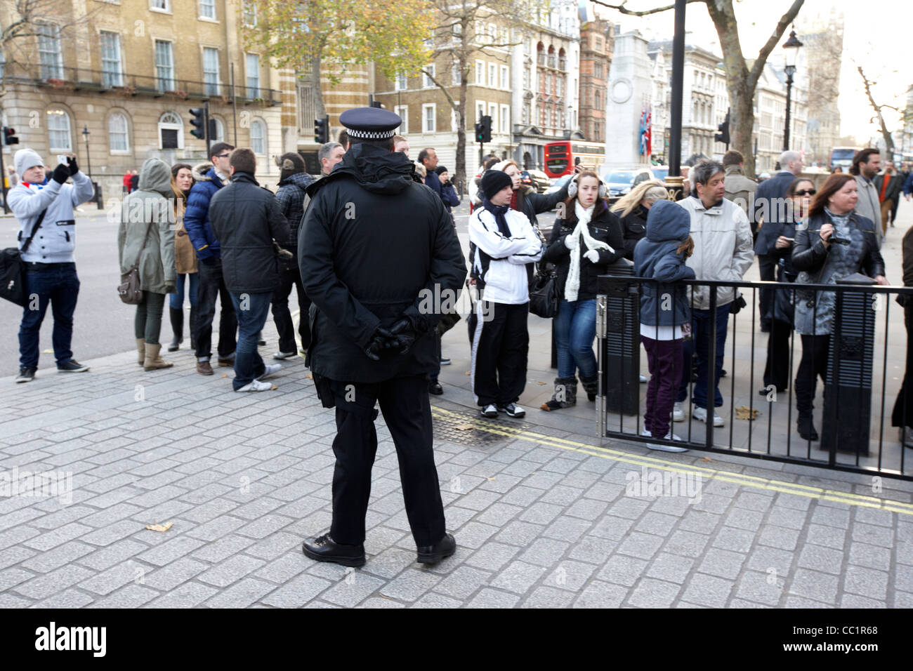metropolitan police officer stands guard watching tourists outside the gates of downing street at whitehall London Stock Photo