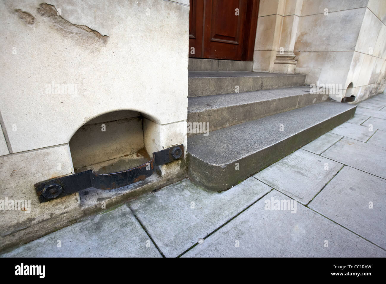 antique boot scraper built into the wall of a historic old office building steps London England UK United kingdom - Stock Image