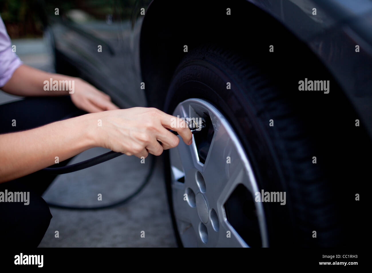 Woman fills tire in car - Stock Image