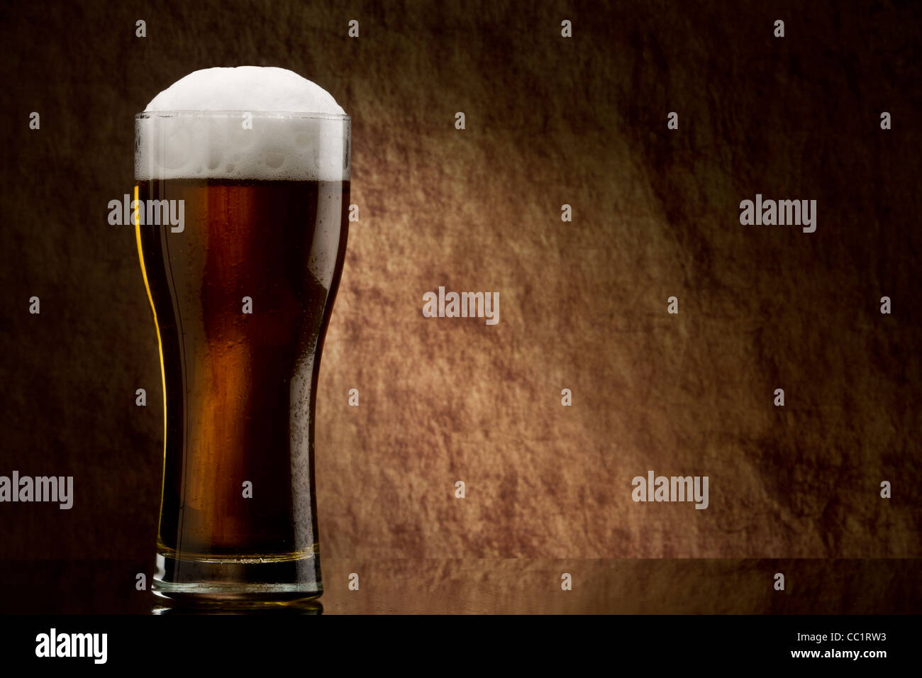 Beer into glass on a old stone - Stock Image