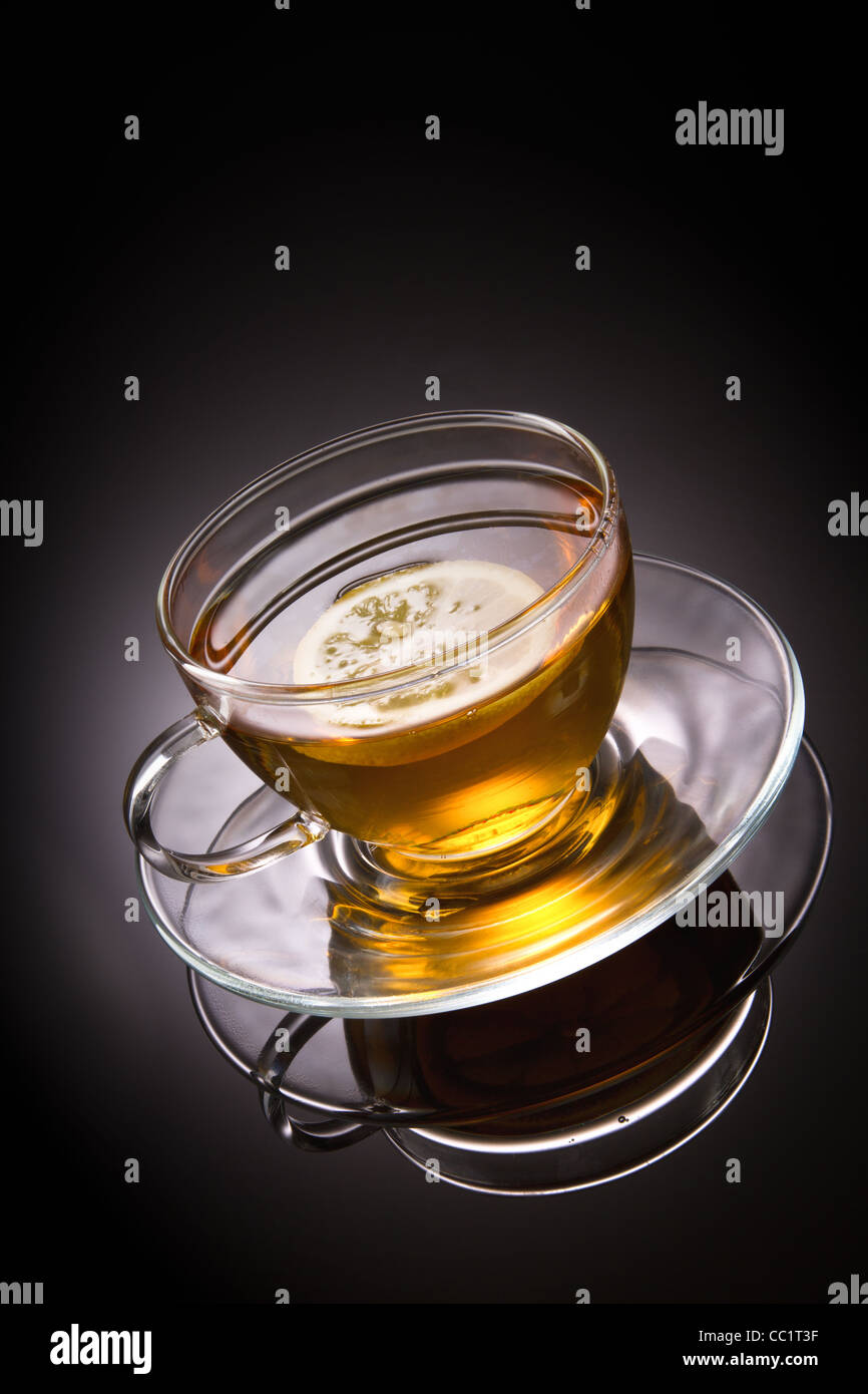 tea with lemon in glass cup on grey background - Stock Image