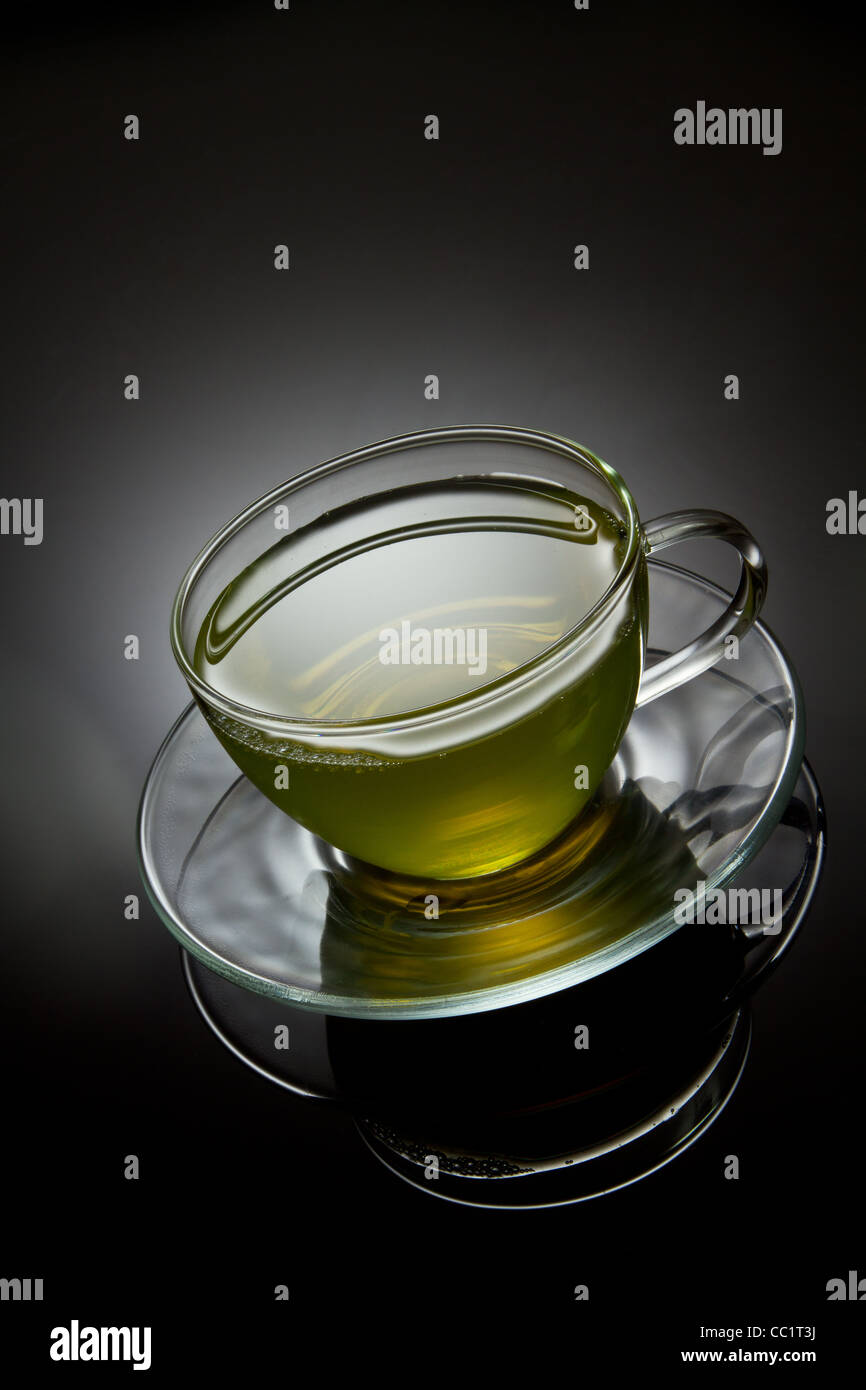 Green tea in glass cup on grey background - Stock Image