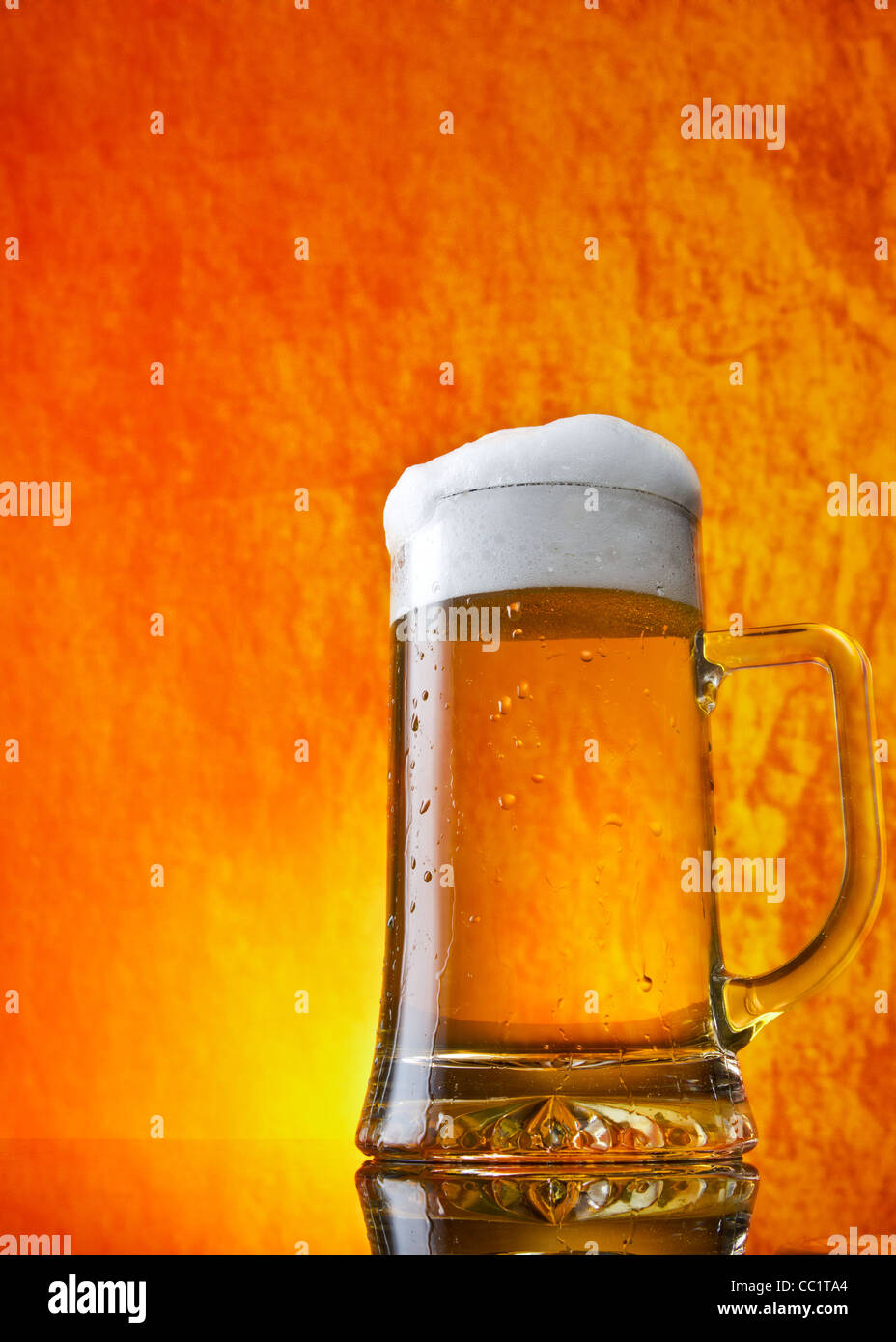 Glass of beer close-up with froth over orange background - Stock Image