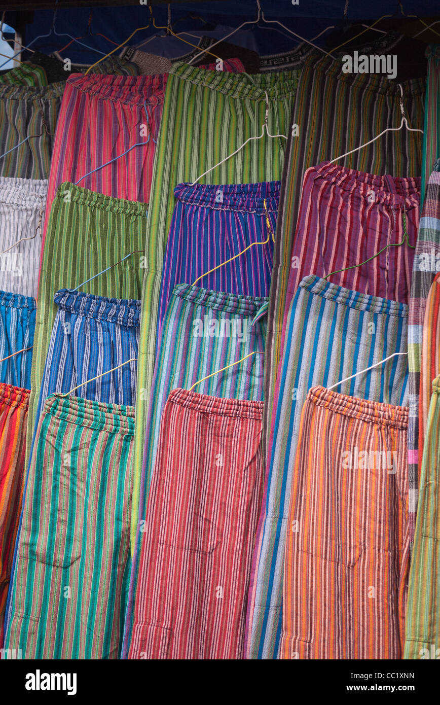 A variety of very colorful cloth pants hang in a display at the market in Otavalo, Ecuador. - Stock Image