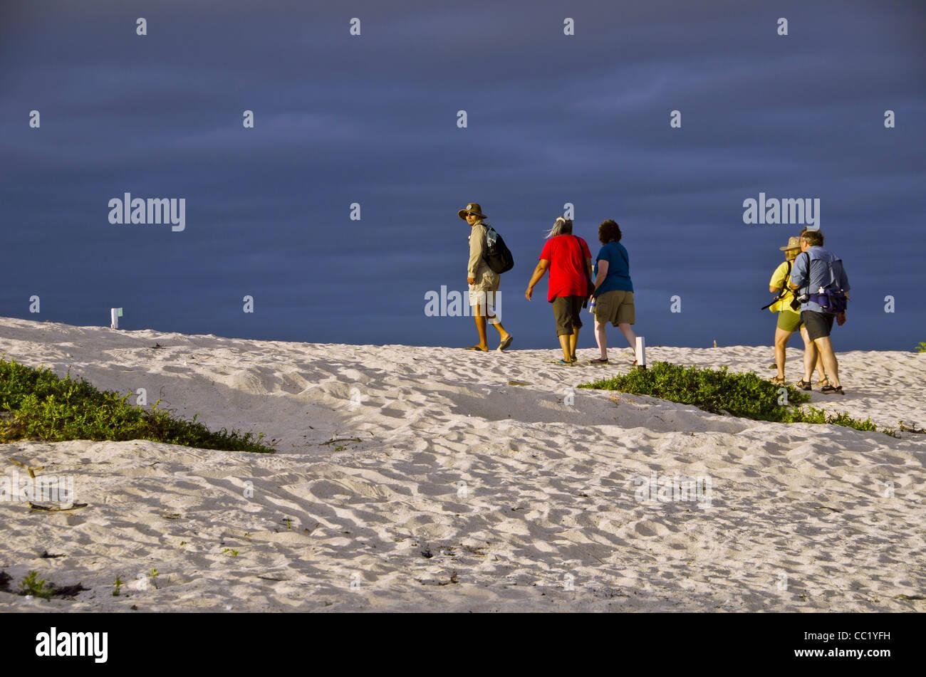Tourists walking on Las Bachas Beach, Santa Cruz Island, Galapagos Islands, Ecuador - Stock Image