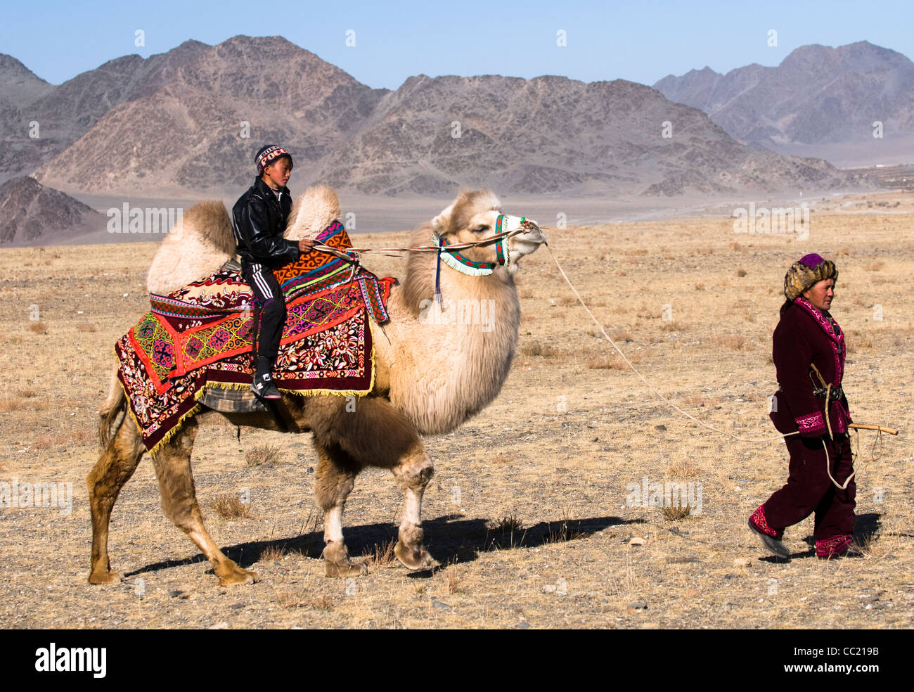 A Kazakh herder with his son in the vast steppe of the Altai region of Western Mongolia. - Stock Image