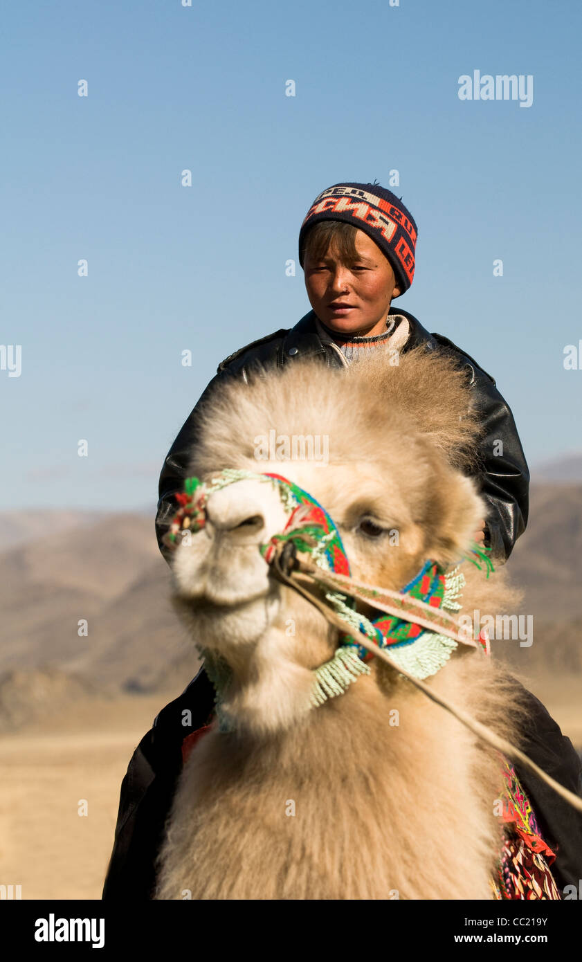 A Kazakh boy riding a  double hump camel in the Altai region of Western Mongolia. - Stock Image