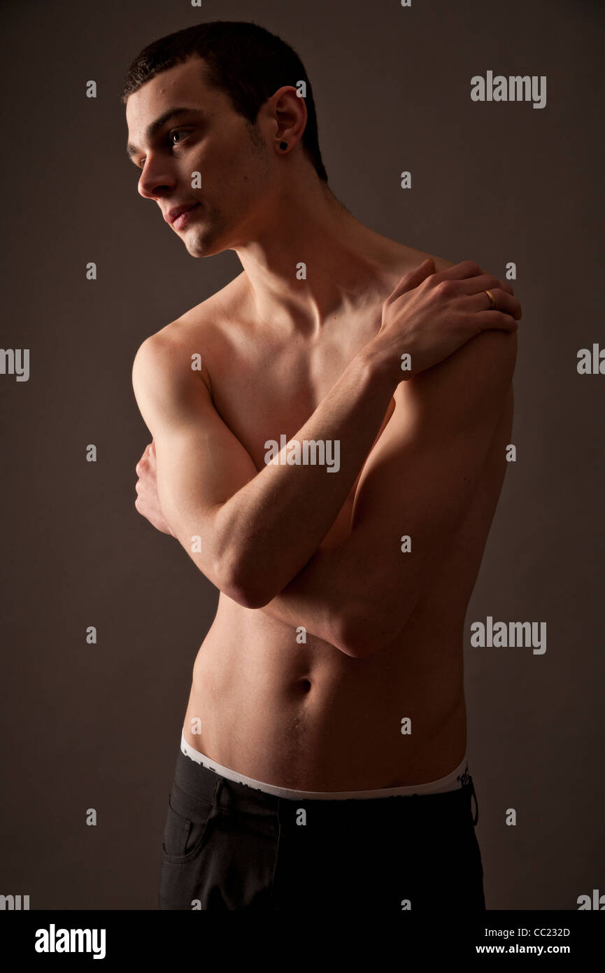 A Slim Thin Slender Late Teen Boy Young Man Adult Looking Sensitive Arms Folded Accross His Chest Uk