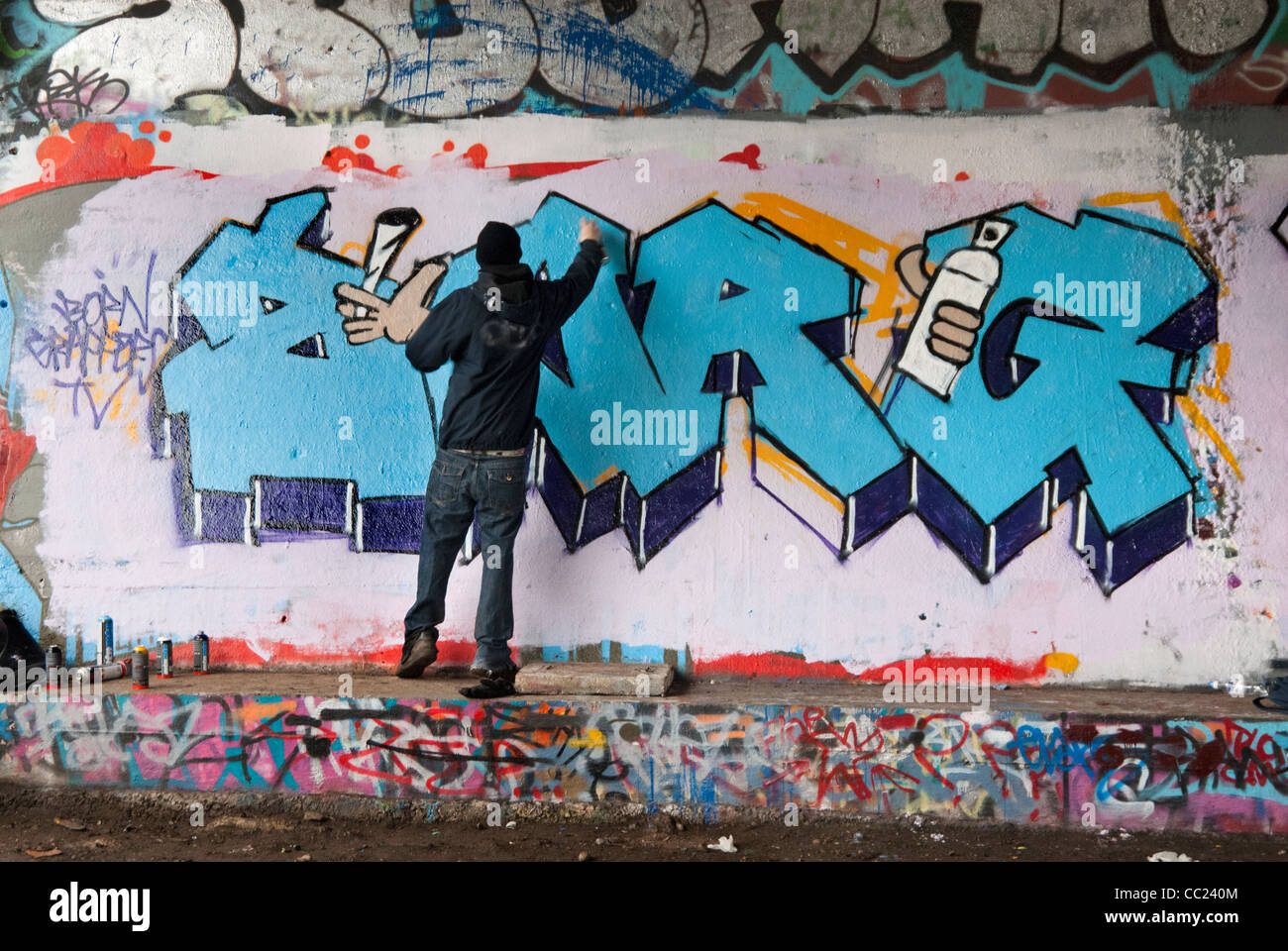 Tagging Hooded Young Man Spray Painting Graffiti Under Bridge