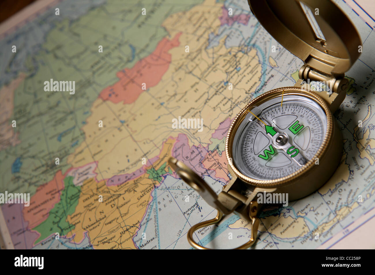 A compass on the world map of the atlas. - Stock Image