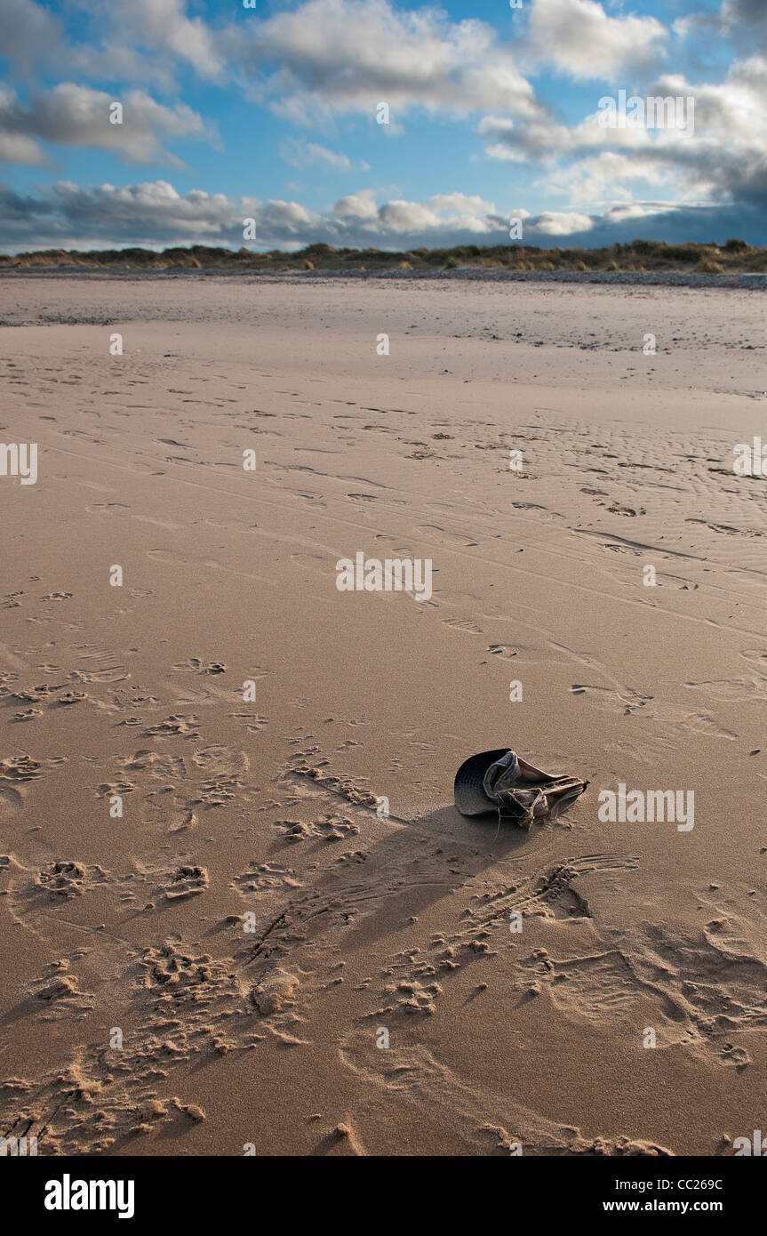 Abandoned cap and footprints on beach, with shadow cast by afternoon light - Stock Image