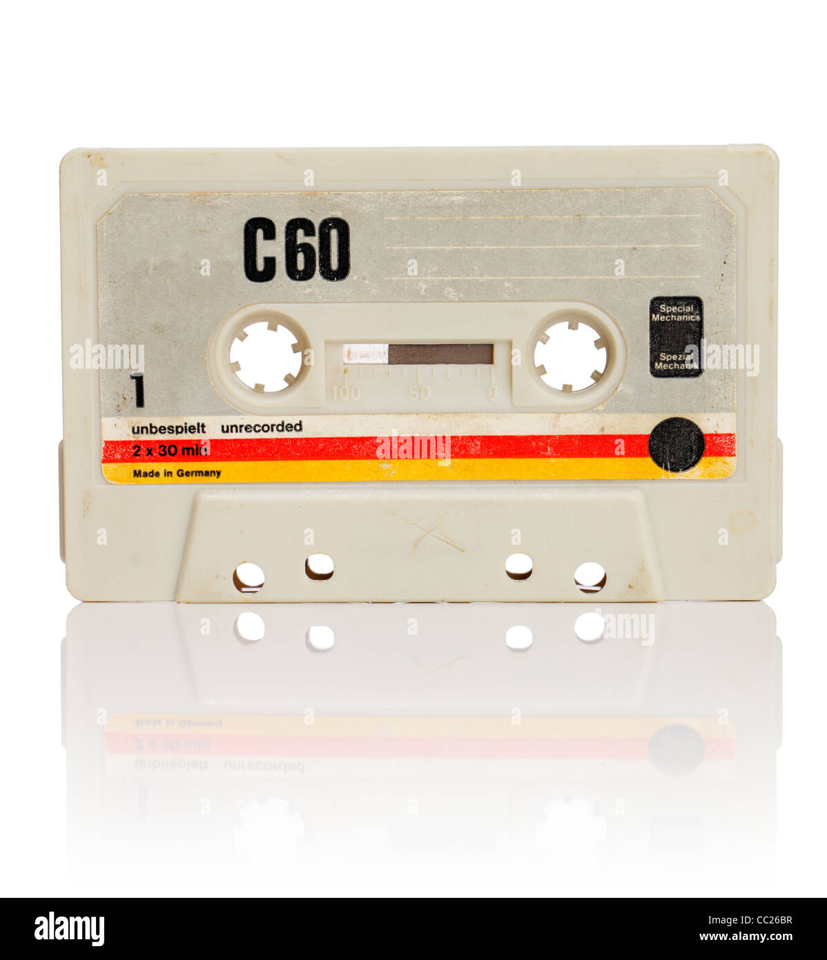 Vintage compact cassette audio tape on white with natural reflection. - Stock Image