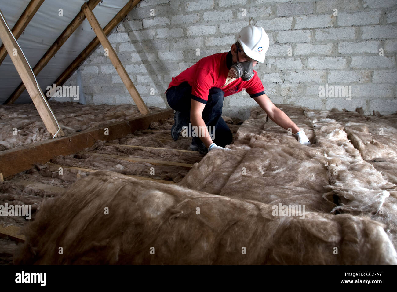 A worker lays loft insulation in the attic of a residential property - Stock Image