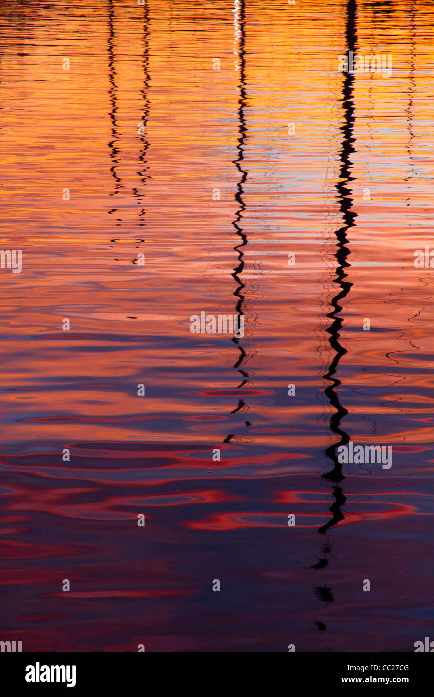 Abstract water reflections of sail boat masts colorful - Stock Image