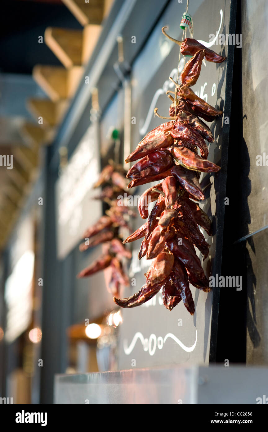Dried chillies hanging in a Delicatessen - Stock Image