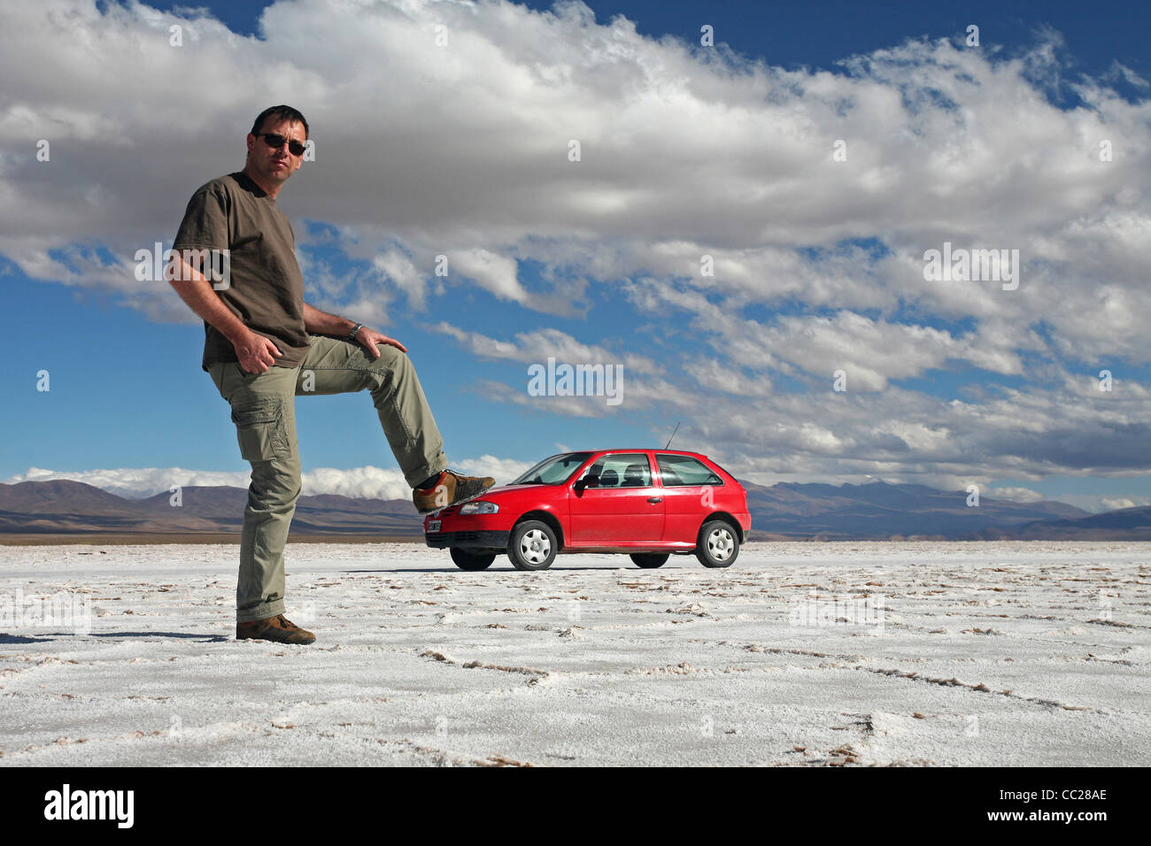 Red car and tourist on the Salar Grande saltflat in the Jujuy province of Argentina Stock Photo