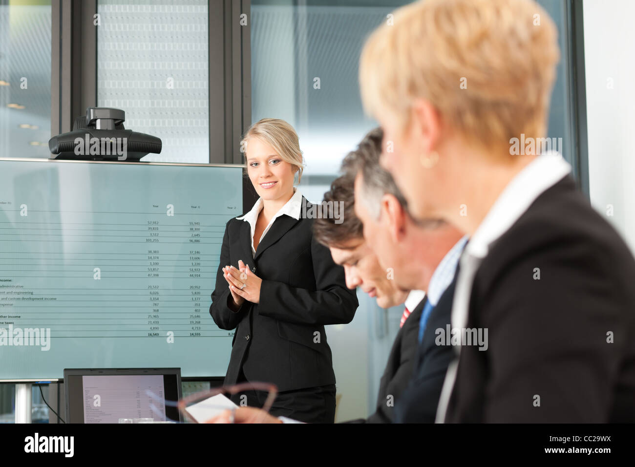 Business - presentation within a team; a female, colleague is standing on the screen - Stock Image