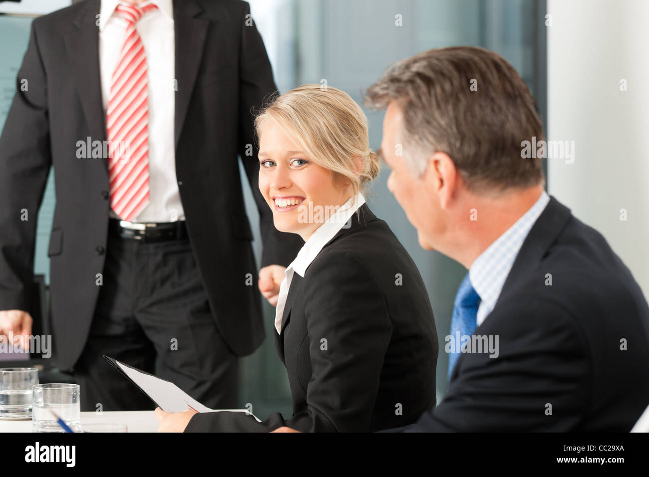 Business - presentation within a team; a male, colleague is standing on the screen - Stock Image